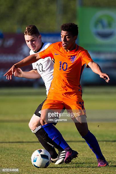 Donyell Malen of Netherlands conducts the ball next to Julian Schwermann of Germany during the U18 international friendly match between Netherlands...