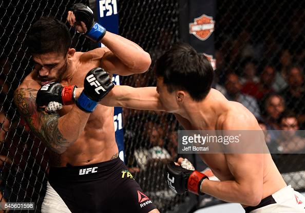 Doo Ho Choi of South Korea knocks down Thiago Tavares of Brazil with a punch in their featherweight bout during The Ultimate Fighter Finale event at...