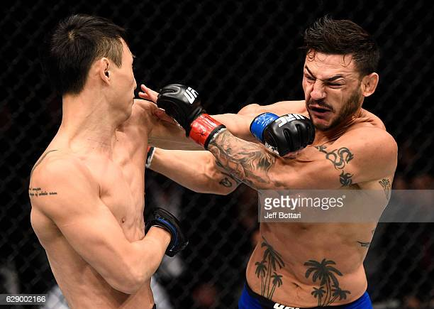 Dooho Choi of South Korea and Cub Swanson trade punches in their featherweight bout during the UFC 206 event inside the Air Canada Centre on December...