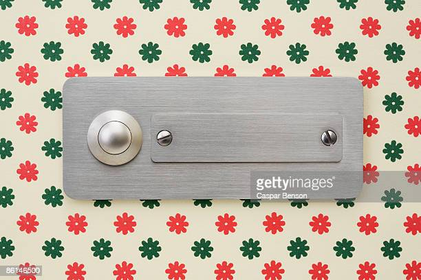 A door buzzer and name plate fixed to a wallpapered wall