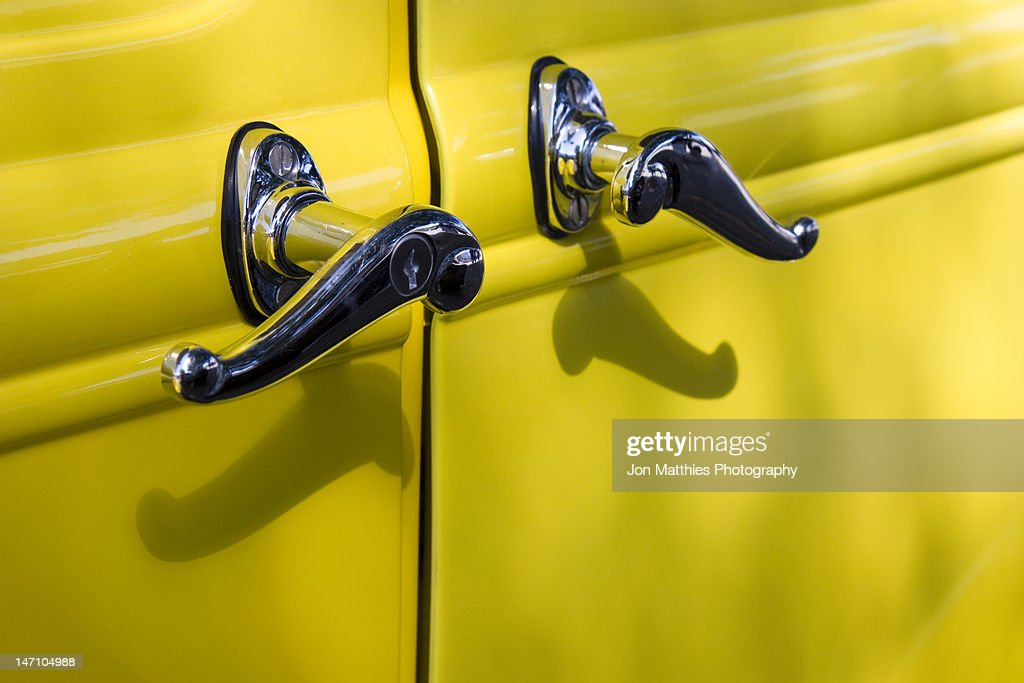 Door handles on an antique yellow car : Stock Photo