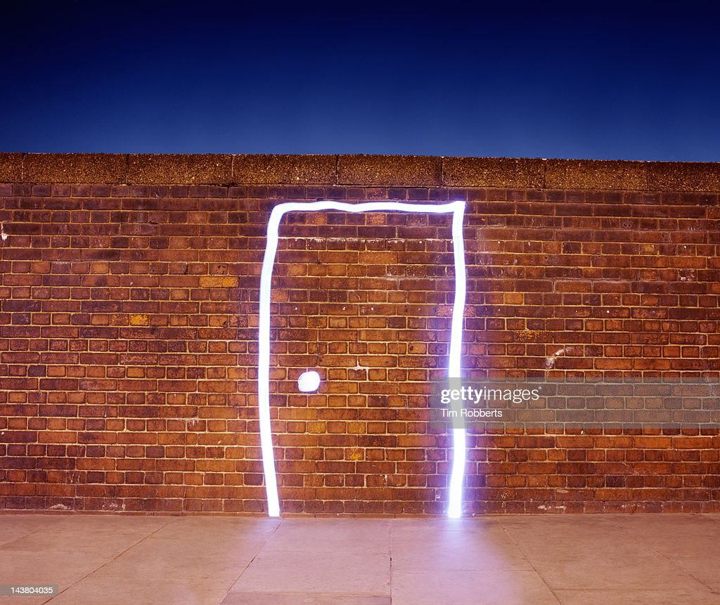 Door made of light on brick wall.