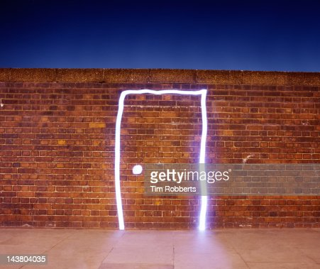 Door made of light on brick wall. : Stock Photo