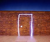 Door made of light on brick wall.