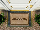 Door mat with welcome word standing in front of the house door