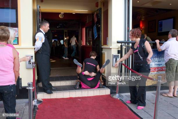 A door security man watches two women out in Blackpool with a hen party fool about on the floor of Nellie Deans Piano Bar on the North Promenade A...