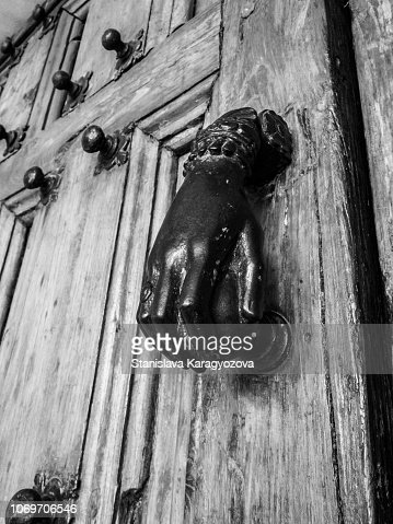 Doorknob in the shape of a female hand on a Belgian church door, architectural detail : Stock Photo