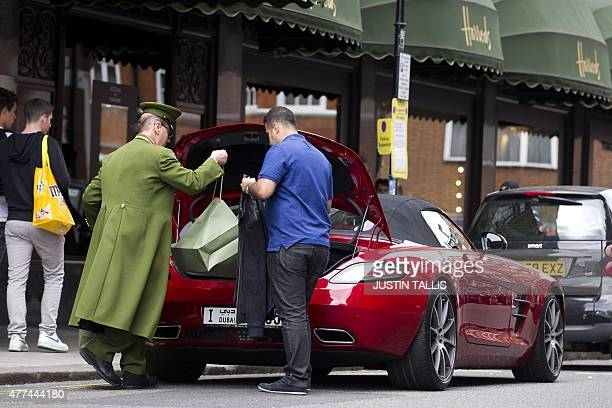 A doorman at Harrods department store puts a customers purchases in the boot of a Dubai registered car in London on June 17 2015 Welcome to London's...