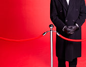 Doorman at red carpet event guarding entrance.