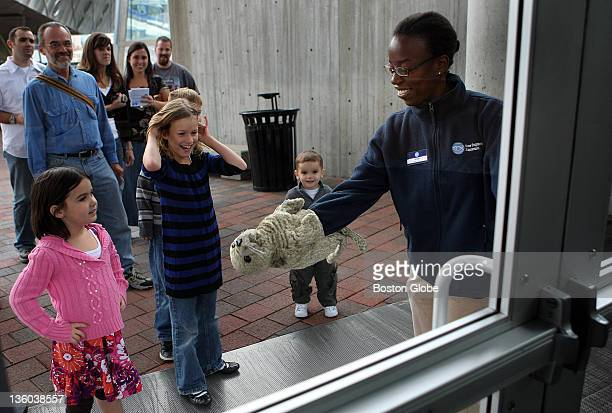 A doorman at the New England Aquarium employee Ariel Martin greets people by the entrance to the New England Aquarium with a harbor seal puppet to...