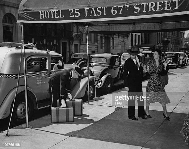 A doorman collecting a couples baggage from a taxi outside a hotel on East 67th Street in New York City circa 1940