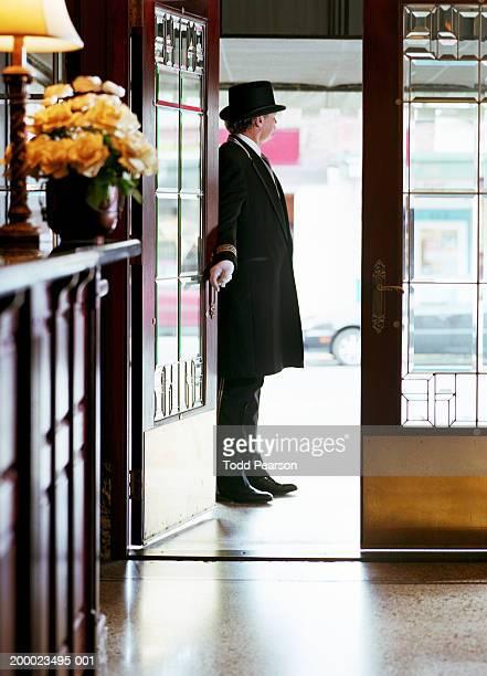 Doorman holding hotel door open, view from lobby