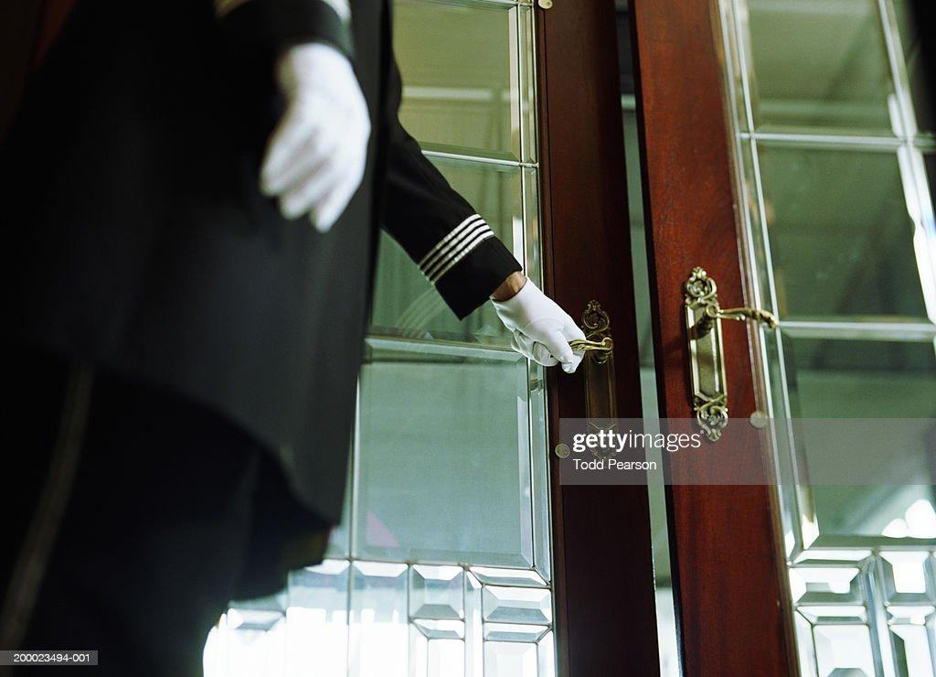 Doorman opening hotel door, mid section