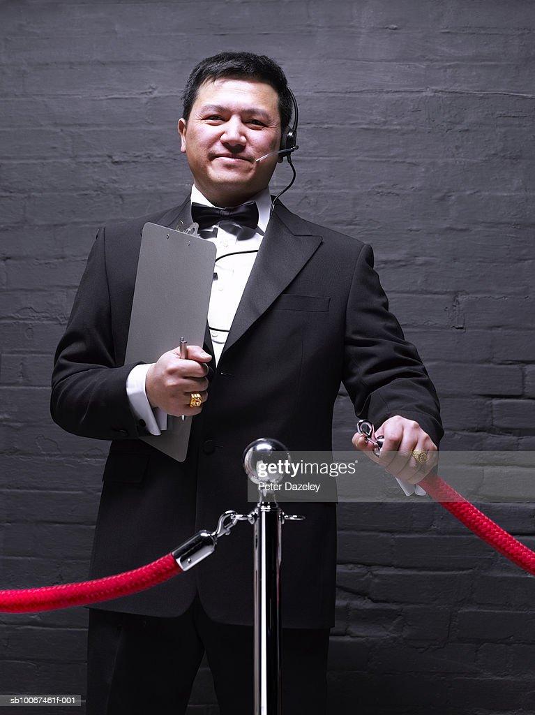 Doorman opening rope barrier, smiling, portrait : Stock Photo