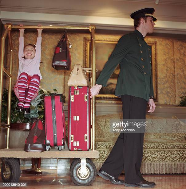 Doorman pulling luggage cart in lobby, girl (4-6) playing on cart
