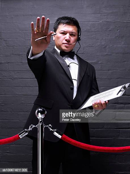 Doorman standing behind rope barrier, gesturing, portrait