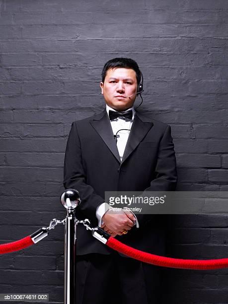 Doorman standing behind rope barrier, portrait