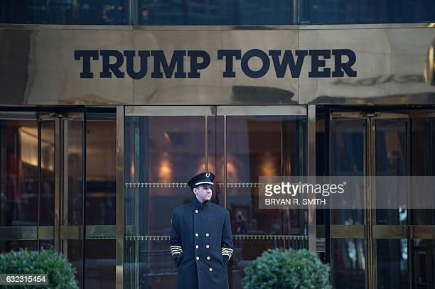 A doorman stands in front of Trump Tower during the Women's March in New York City on January 21 2017 in New York Hundreds of thousands of people...