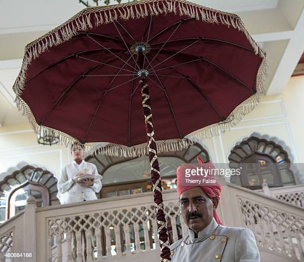 A doorman with a umbrella welcomes guests at the Rambagh Palace in Jaipur a former residence of the Maharaja of Jaipur and now a luxury Hotel