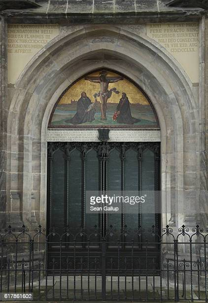 Doors made of a cast metal reproduction of Martin Luther's 95 theses stand in the doorway where in 1517 Luther originally nailed his theses at the...