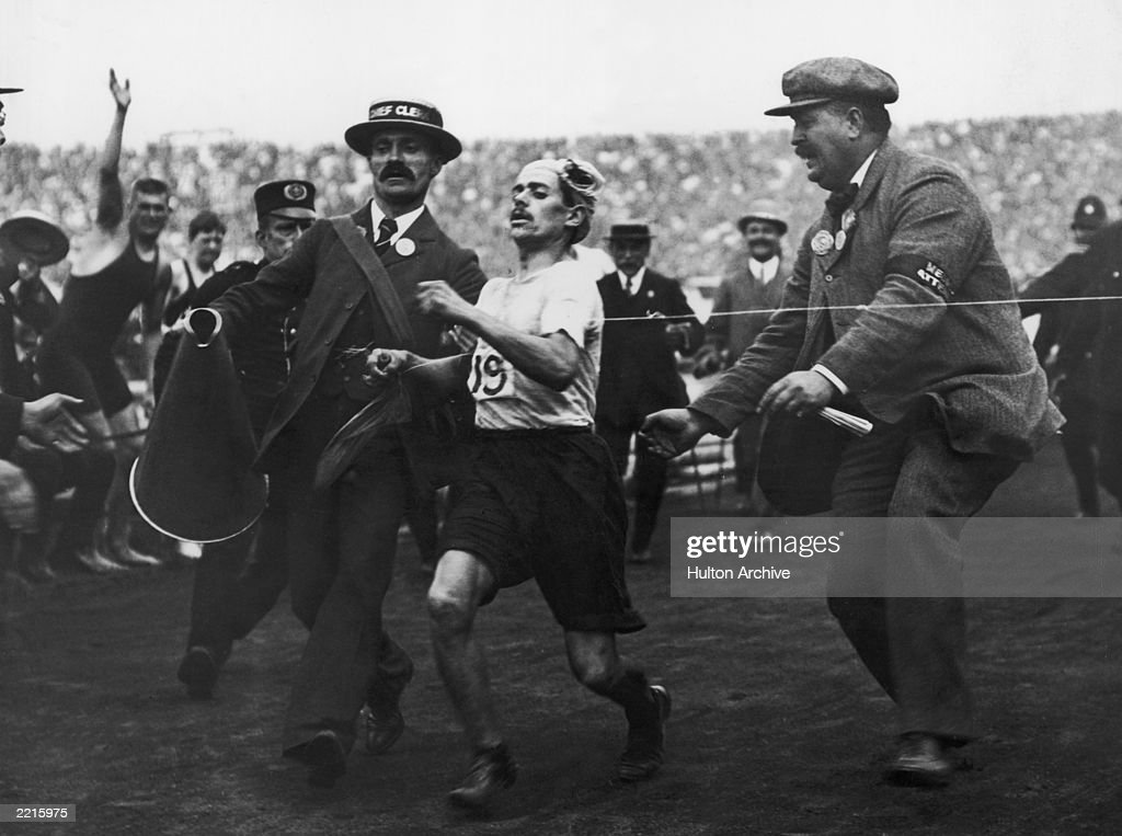 Dorando Pietri of Italy, on the verge of collapse, is helped across the finish line in the Marathon event of the Olympic Games in London, 24th July 1908. He was subsequently disqualified and the title was given to John Hayes of the USA.