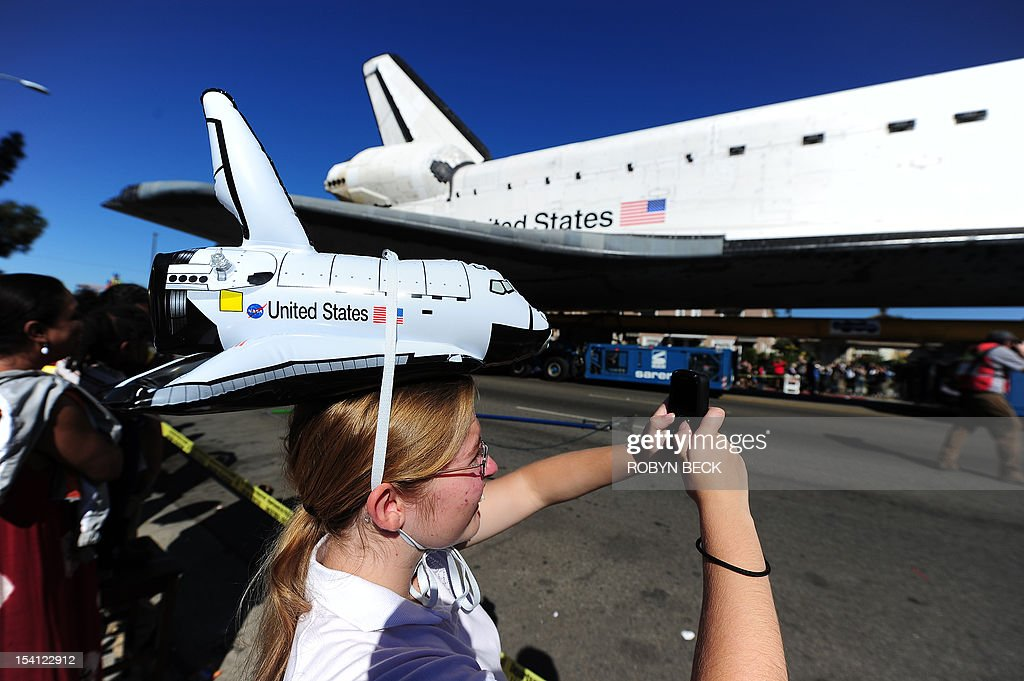 Doreen Andreotti photographs the Space Shuttle Endeavour as it nears the end of its journey to the California Science Center in Exposition Park in Los Angeles October 14, 2012. The 170,000-pound (77,272 kg) shuttle completed its 12-mile (19km) road trip from Los Angeles International Airport to its permanent museum home just over 18 hours late. AFP PHOTO / Robyn Beck