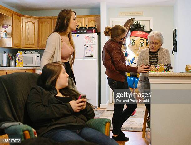 Doreen Farrington looks at earnings her daughter Ashley found online on her phone at their home in South China ME on Monday March 30 2015 Farrington...
