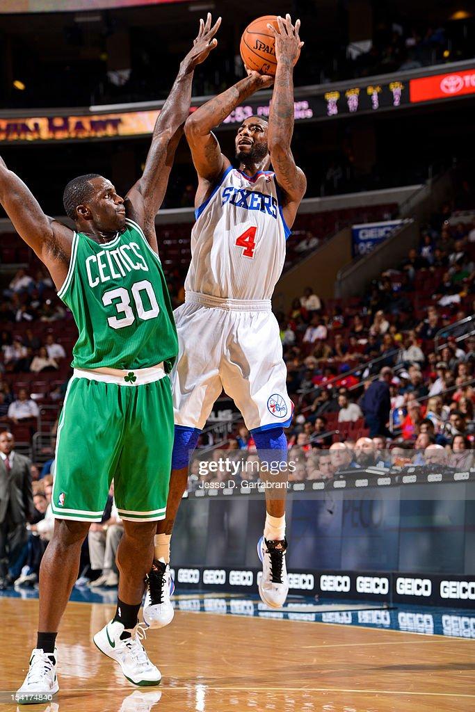 Dorell Wright #4 of the Philadelphia 76ers shoots against Brandon Bass #30 of the Boston Celtics during a pre-season game at the Wells Fargo Center on October 15, 2012 in Philadelphia, Pennsylvania.