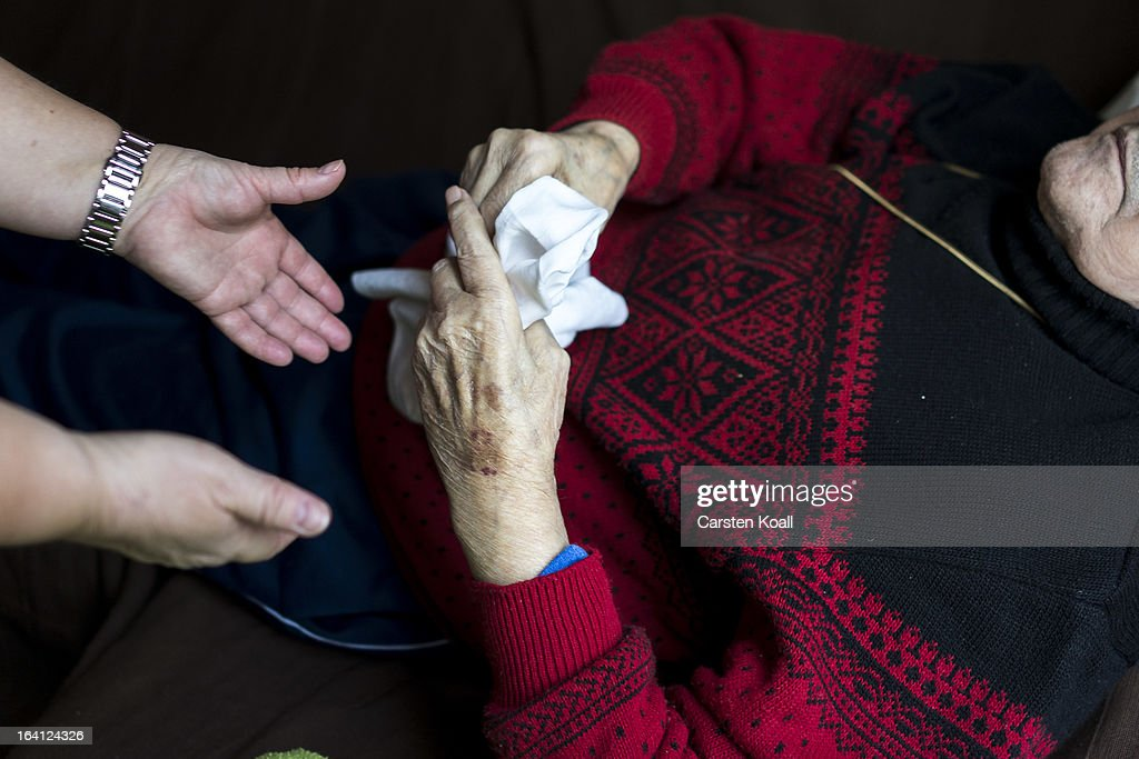 Doret Kohl nurse of the German Red Cross attends to a patient in the geriatric day care facility at Villa Albrecht on March 18 2013 in Berlin Germany...
