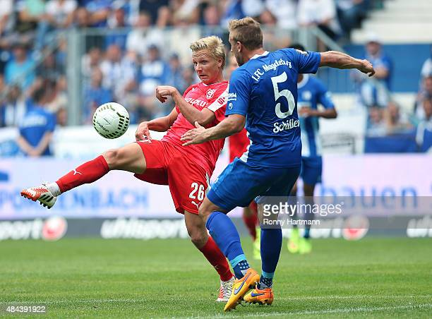 Dorian Diring of Halle vies with Felix Schiller of Magdeburg during the Third League match between 1 FC Magdeburg and Hallescher FC at MDCCArena on...