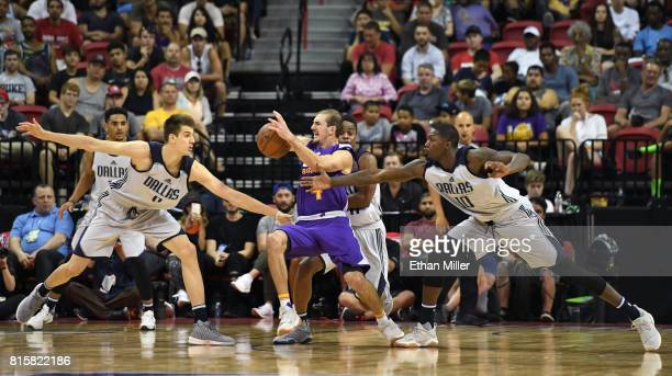 Dorian FinneySmith of the Dallas Mavericks knocks the ball away from Alex Caruso of the Los Angeles Lakers as Nicolas Brussino of the Mavericks...