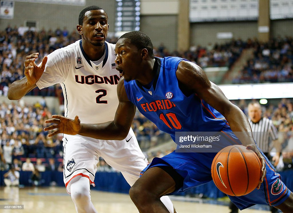 Dorian Finney-Smith #10 of the Florida Gators drives underneath the basket in front of DeAndre Daniels #2 of the Connecticut Huskies in the first half during the game at Harry A. Gampel Pavilion on December 2, 2013 in Storrs, Connecticut.