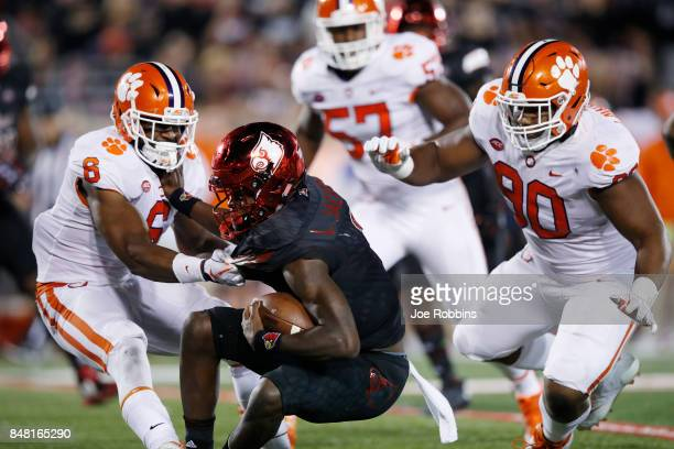 Dorian O'Daniel and Dexter Lawrence of the Clemson Tigers tackle Lamar Jackson of the Louisville Cardinals in the third quarter of a game at Papa...