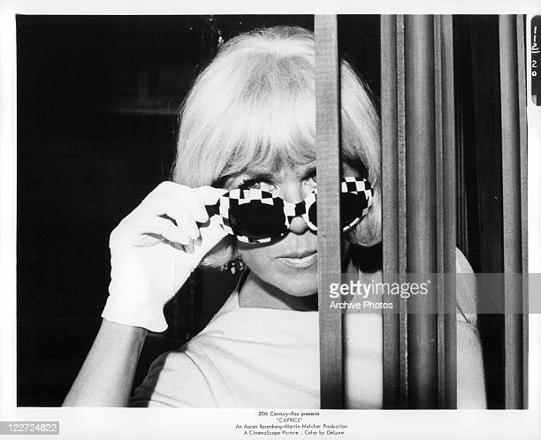 Doris Day adjusting her sunglasses in a scene from the film 'Caprice' 1967