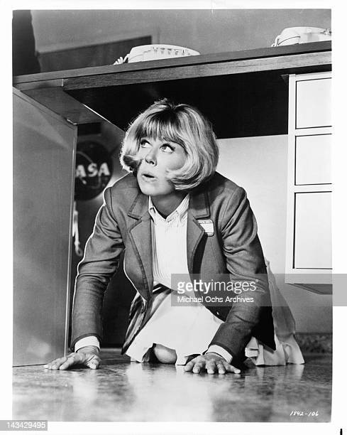 Doris Day finds herself in a strange position as she eavesdrops from under her bosses desk in a scene from the film 'The Glass Bottom Boat' 1966