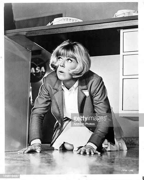 Doris Day hiding under office desk in a scene from the film 'The Glass Bottom Boat' 1966