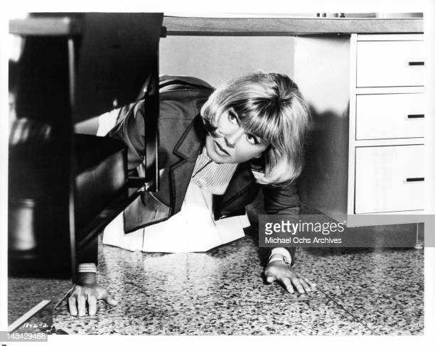 Doris Day under a desk trying to escape a persistent suitor in a scene from the film 'The Glass Bottom Boat' 1966