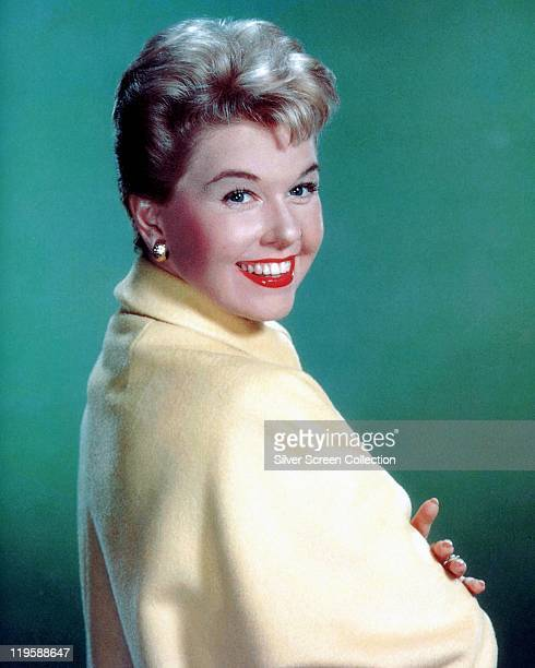 Doris Day US actress and singer smiling wearing a yellow shawl in a studio portrait against a green background circa 1960