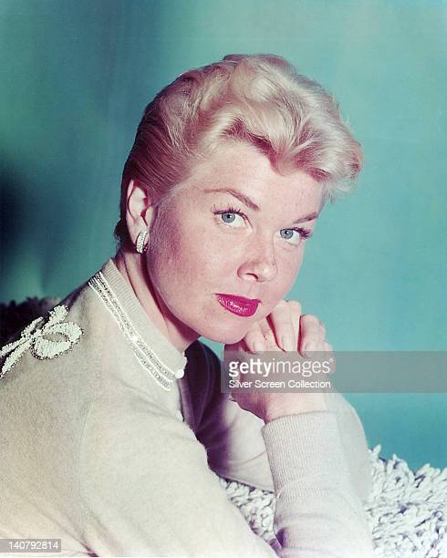 Doris Day US actress and singer wearing a cream jumper posing with her hands clasped together in front of her in a studio portrait against a light...