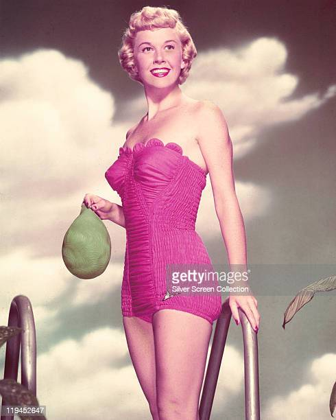 Doris Day US actress and singer wearing a pink swimsuit and holding a green swimming cap circa 1955
