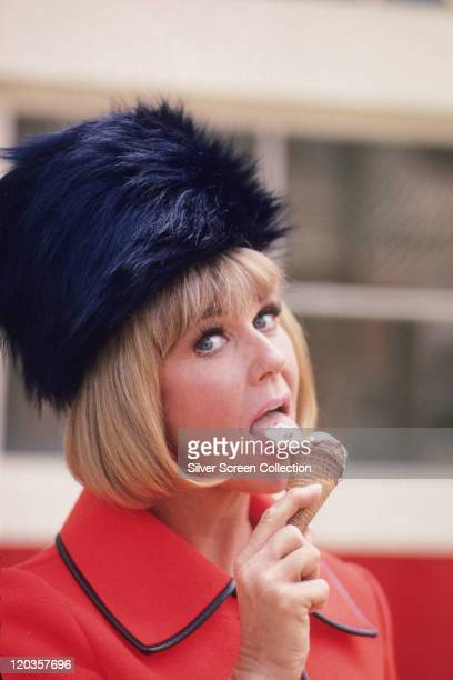 Doris Day US actress and singer wearing a red jacket with black trim and a black fur hat while licking an ice cream in a cone circa 1960