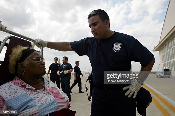 Doris Kendricks of New Orleans LA speaks with San Antonio fireman Marcelo Uriegas after arriving from New Orleans on September 2 2005 at Kelly USA in...