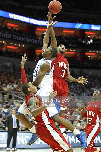 Doron Lamb of the Kentucky Wildcats drives for a shot attempt against Derrick Gordon and Kahlil McDonald of the Western Kentucky Hilltoppers in the...
