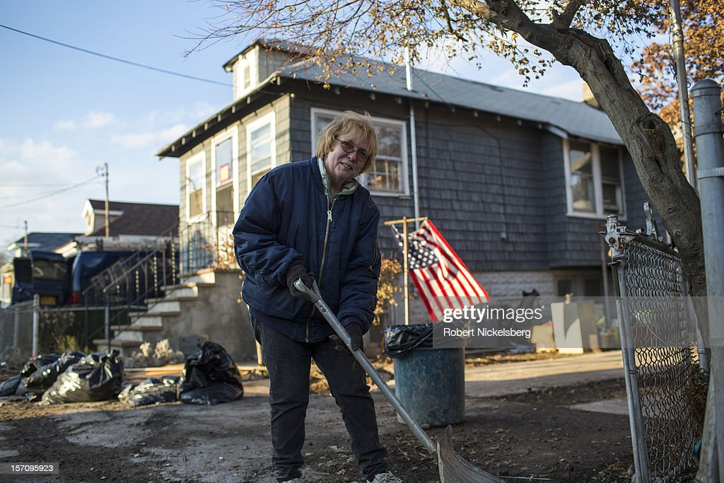 Dorothy Cavallero cleans the outside of her father's residence November 28, 2012 in a residential area of New Dorp Beach in the Staten Island borough of New York City. Parts of the New Dorp neighborhood were submerged under 10 feet of water during the height of Superstorm Sandy one month ago.