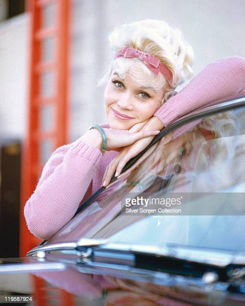 Dorothy Provine US actress and comedienne wearing a pink woollen jumper with a pink bow in her hair leaning aganst the windscreen of a car circa 1960