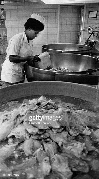 JUN 29 1983 Dorothy Spanks empties part of the 670 lbs of chicken breasts into vats to be cooked