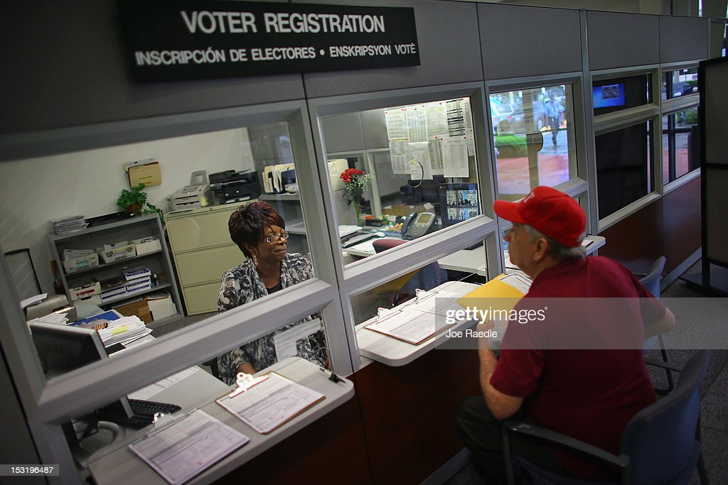 Dorothy Torrence from the MiamiDade Elections Department helps Alvaro Arochena fill out his registration form on October 1 2012 in Miami Florida With...
