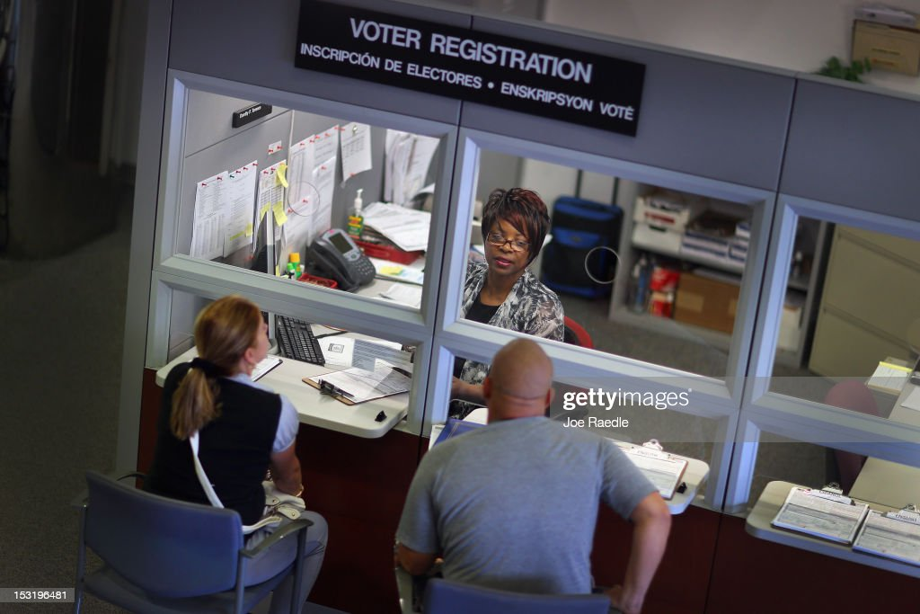 Dorothy Torrence from the MiamiDade Elections Department helps Yarelis Alvarez and Alberto Alvarez fill out their voter registration forms on October...