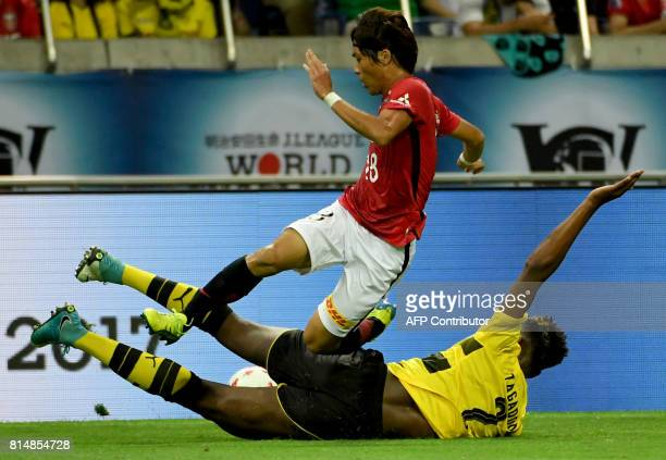 Dortmund defender DanAxel Zagadou fights for the ball with Urawa Reds midfielder Yoshiaki Komai during their friendly football match between Japan's...