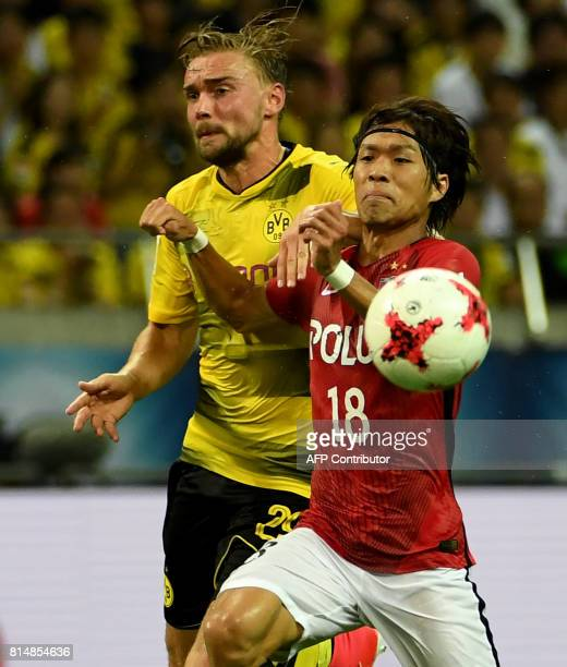 Dortmund defender Marcel Schmelzer fights for the ball with Urawa Reds midfielder Yoshiaki Komai during their friendly football match between Japan's...